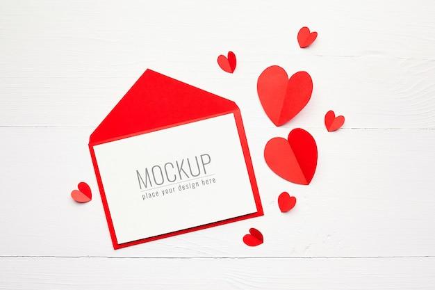 흰색 나무 표면에 봉투와 빨간 종이 마음으로 발렌타인 데이 카드 모형 프리미엄 PSD 파일