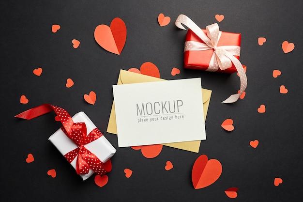 검은 색 표면에 빨간 종이 하트와 선물 상자와 발렌타인 데이 카드 모형 프리미엄 PSD 파일