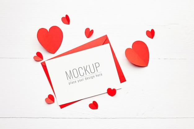 흰색 나무 표면에 빨간 종이 마음으로 발렌타인 데이 카드 모형 프리미엄 PSD 파일