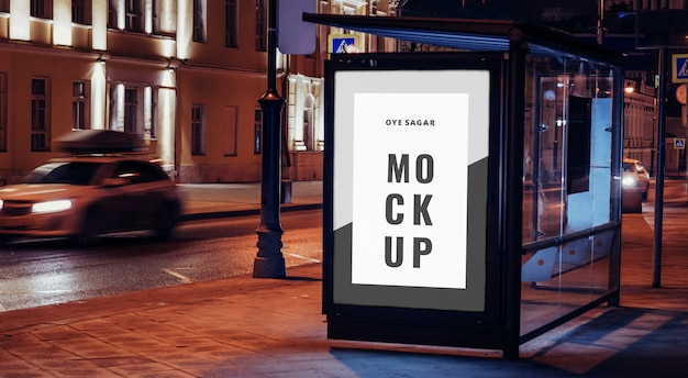 Vertical billboard mockup at bus stop on the night city Premium Psd