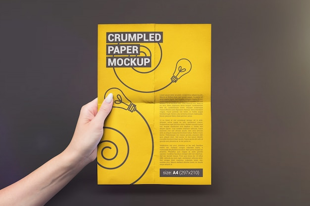手のモックアップで縦に折り畳まれた紙 Premium Psd
