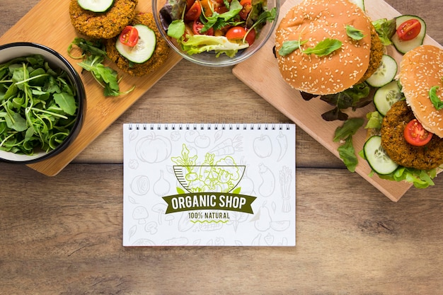 Above view arrangement with burgers and notebook Free Psd
