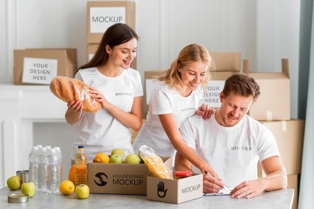 Волонтер записывает еду в коробки для пожертвований Бесплатные Psd