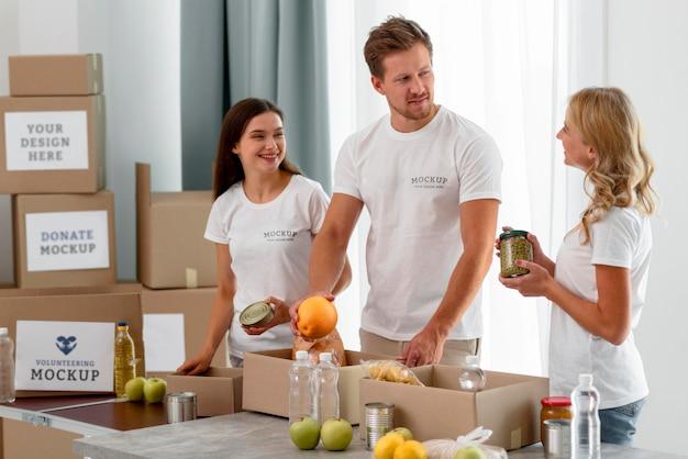 Волонтеры готовят еду в коробках для пожертвований Бесплатные Psd