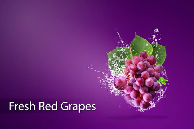 Water splashing on fresh red grapes over red background. Premium Psd