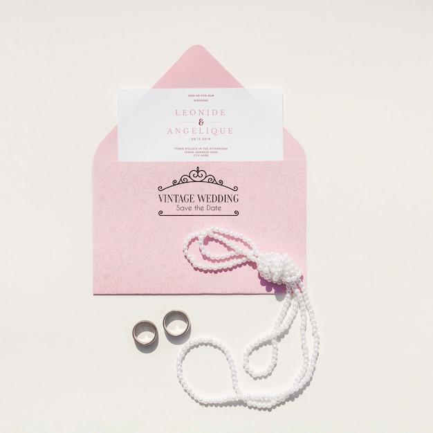 Decorazione di cerimonia nuziale nei toni rosa con busta e fedi nuziali Psd Gratuite