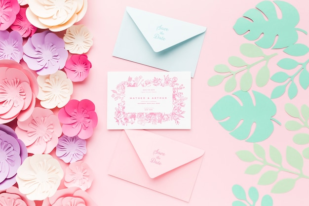 청첩장 모형 및 분홍색 배경에 종이 꽃 봉투 무료 PSD 파일