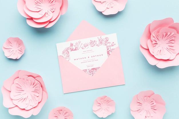 青の背景に紙の花と結婚式の招待状のモックアップ 無料 Psd