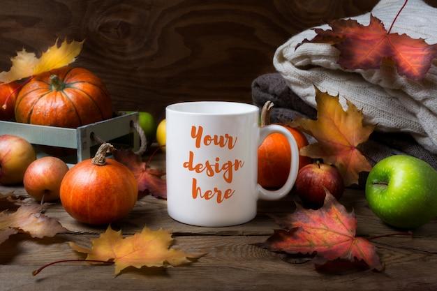 White coffee mug mockup with fall leaves, pumpkins Premium Psd