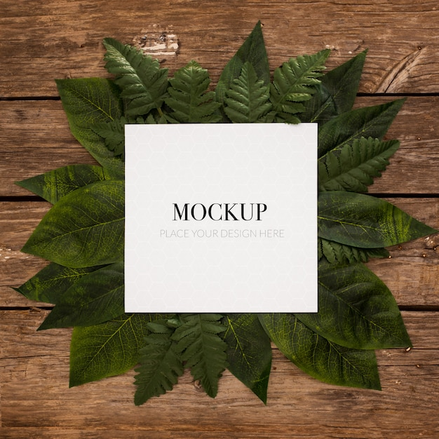 White frame for mockup with border leaves on wood Free Psd