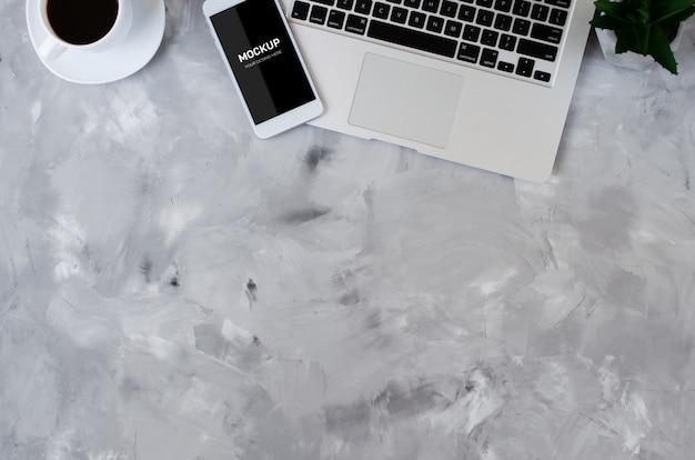휴대용 퍼스널 컴퓨터와 커피 한잔 사무실 책상에 검은 빈 화면이 흰색 스마트 폰. 전화를 비웃습니다. 프리미엄 PSD 파일