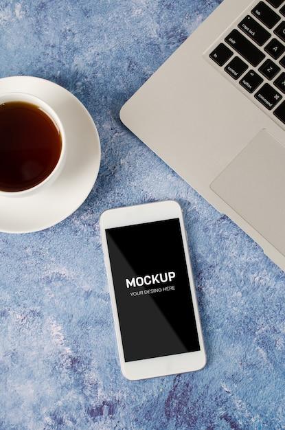 Белый смартфон с черным пустым экраном на офисном столе с ноутбуком и чашкой чая. макет телефона. Premium Psd