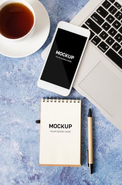 Белый смартфон с черным пустым экраном на офисном столе с ноутбуком, пустой блокнот и чашку чая Premium Psd