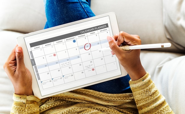 Woman checking calendar on digital tablet Premium Psd