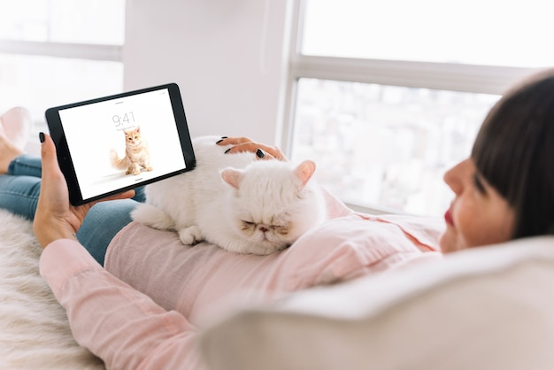 Woman on couch with cat and tablet mockup Free Psd