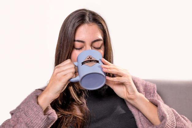 Woman drinking from blue mug Free Psd