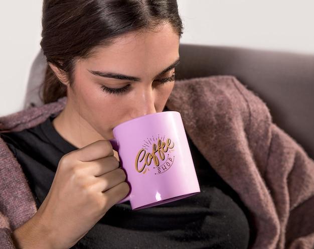 Woman drinking from pink mug Free Psd