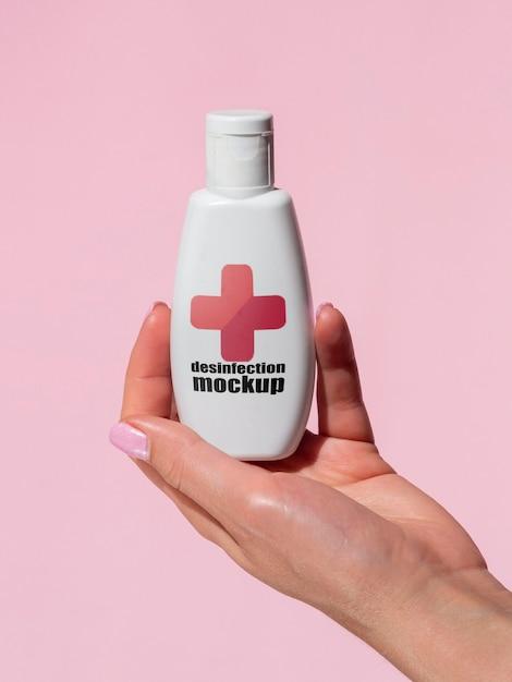 Mano della donna che tiene il mock-up della bottiglia di disinfezione Psd Gratuite