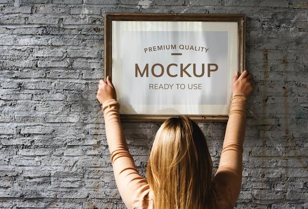 Woman hanging a photo frame mockup Premium Psd
