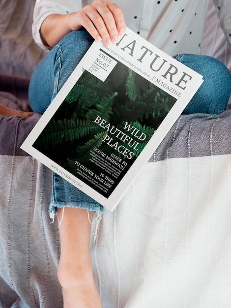 Женщина, держащая журнал о природе рядом с ее ногой Бесплатные Psd