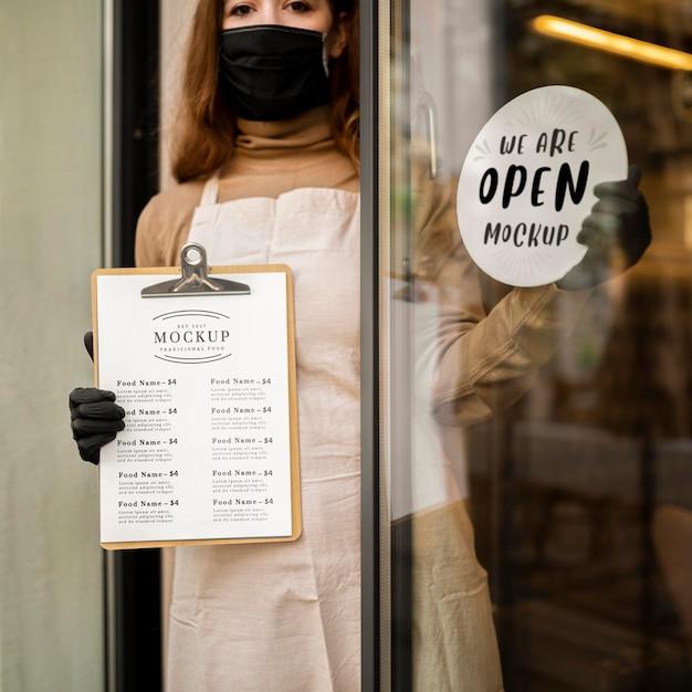 クリップボードにレストランメニューのモックアップを保持している女性 無料 Psd