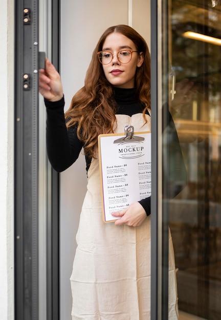 レストランメニューのモックアップを保持している女性 無料 Psd