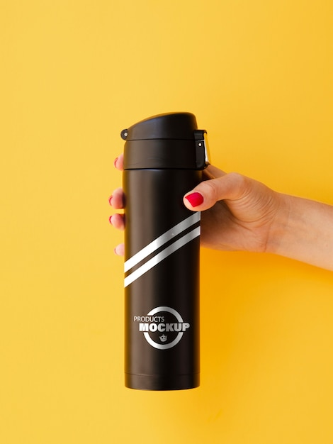 Woman holding a black thermos mock-up on yellow background Free Psd