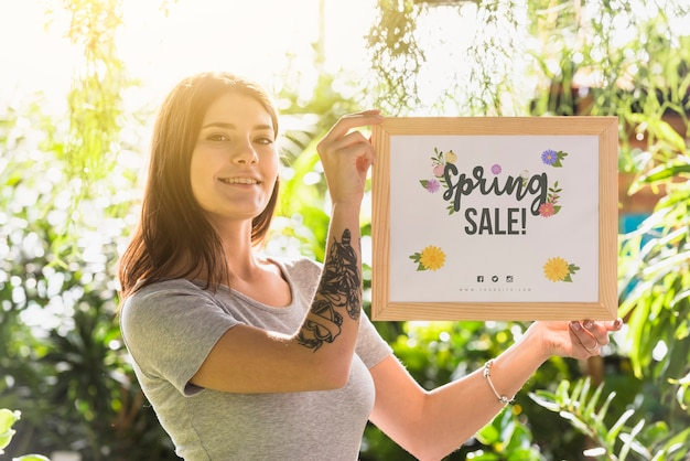 Woman holding board mockup for spring sale Free Psd