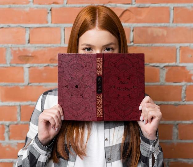 Woman holding book mock-up Premium Psd