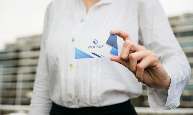 Woman holding business card outdoor Free Psd