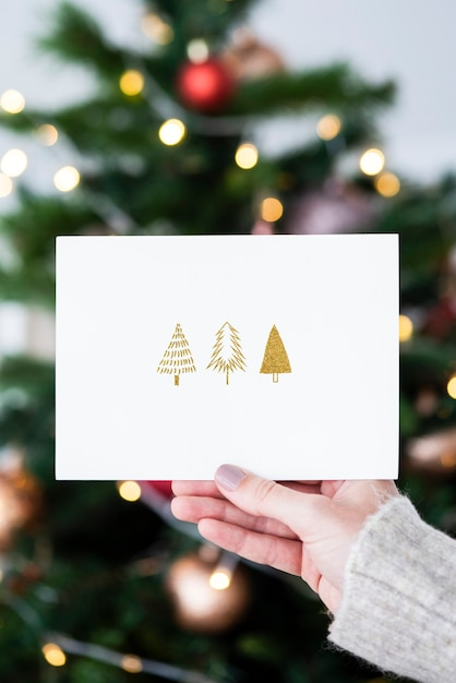 Woman holding a christmas card in front of a christmas tree mockup Free Psd