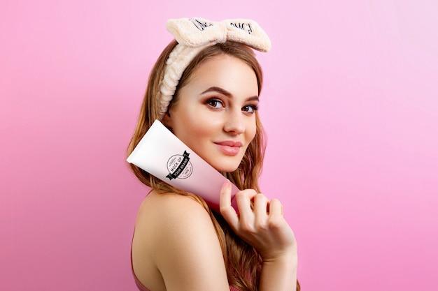 Woman holding cream tube mockup Premium Psd