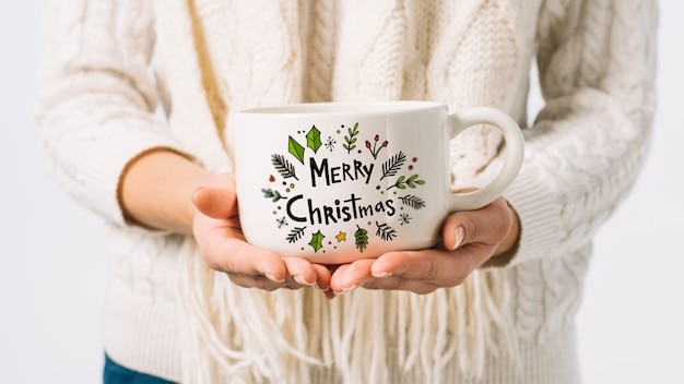 Woman holding cup mockup with christmas concept Free Psd