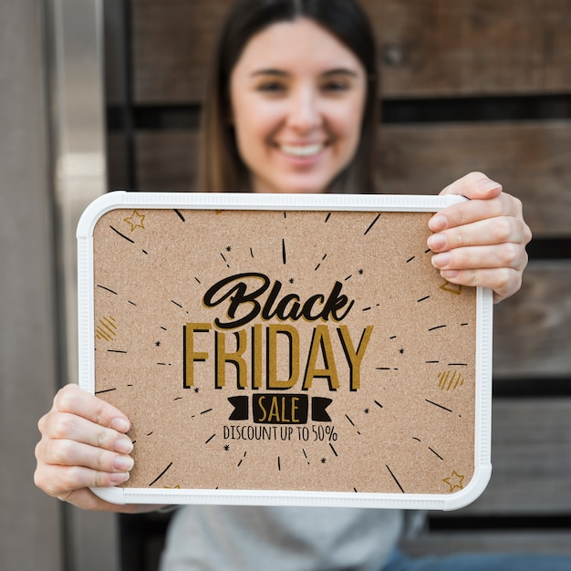 Woman holding frame mockup with black friday concept Free Psd