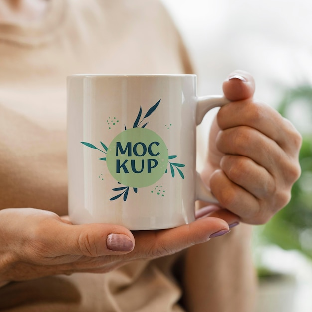 Woman holding a mock-up mug in her urban orchard Free Psd