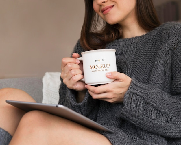 Woman holding a mug mock-up in winter Free Psd