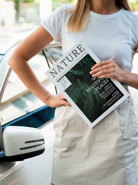 Woman holding a nature magazine next to a car Free Psd