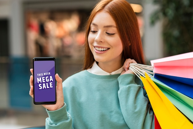 Woman holding paper bags and looking at her phone Free Psd