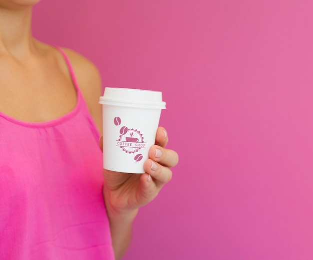Woman holding paper coffee cup mock-up with copy space Free Psd