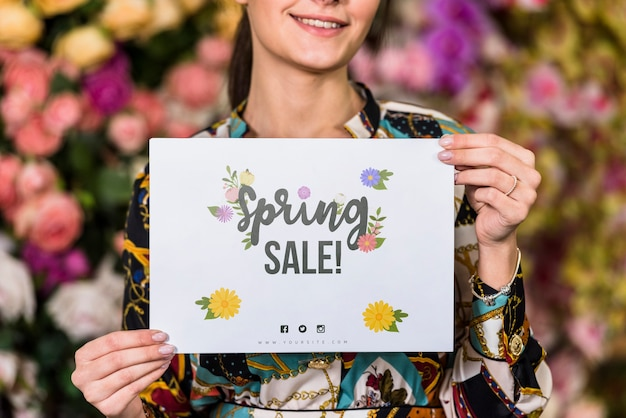 Woman holding paper mockup for spring sale Free Psd