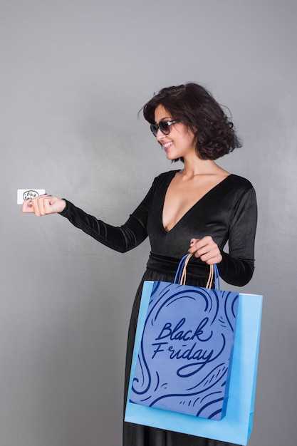 Woman holding shopping bag mockup with black friday concept Free Psd