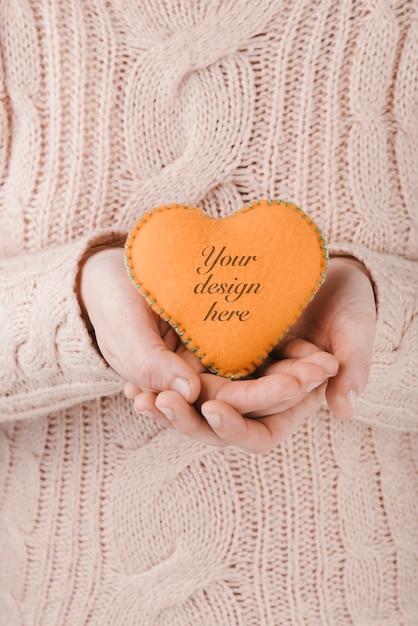Donna che tiene un piccolo cuore fatto a mano Psd Gratuite