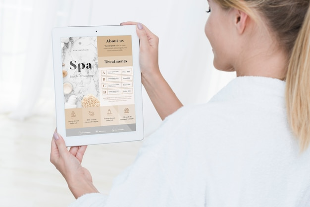 Woman holding tablet mock-up with spa offers Free Psd