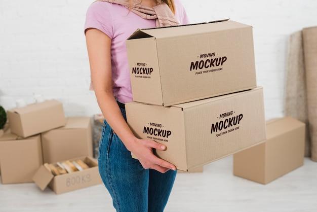 Donna che mantiene due scatole per trasloco mock-up Psd Gratuite