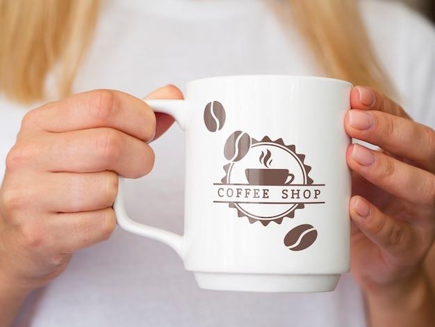 Woman holding up a coffee mug mock-up Free Psd