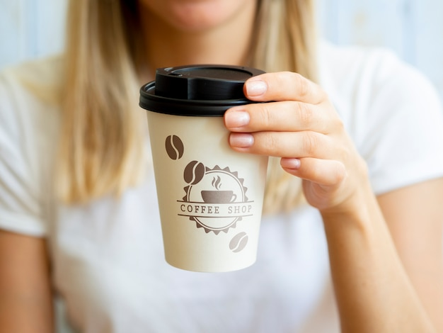 Woman holding up a coffee paper cup Free Psd