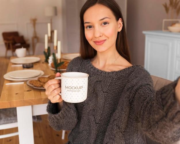 Woman holding a white mug mock-up Free Psd