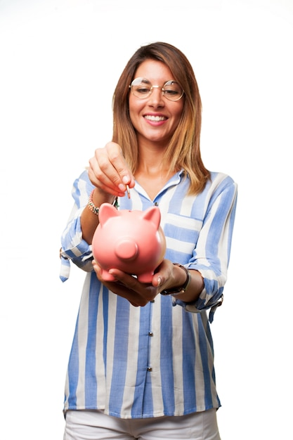 Woman inserting a coin into piggy bank Free Psd