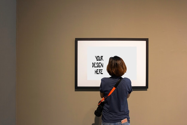 Woman is looking at blank photo frame on wall in art gallery Premium Psd