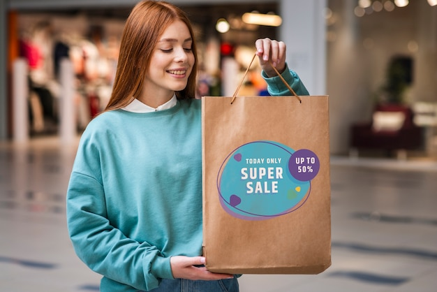 Woman in a mall holding a big paper bag filled with products on sale Free Psd